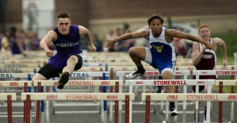 Strasburg's Elijah Waters, left, edges out Central's Daniel George in the 110-meter hurdles during the county track meet at Quicksburg Wednesday evening. Rich Cooley/Daily